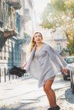 Ung stilfull kvinna som går på stadsgatan royaltyfri bild