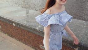 Ung stilfull kvinna som går på stranden i staden stock video
