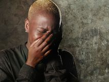 Ung stilfull ledsen och deprimerad afro amerikansk svart kvinnagråt i förtvivlanbeläggningframsida med händer som känner sig bedr arkivfoto
