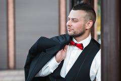 Ung stilfull man i en dräkt Stående av brudgummen Brudgummen rymmer hans omslag på hans skuldra, sidosikt royaltyfria bilder