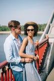 ung stilfull man i solglasögon som omfamnar den afrifcan amerikanska flickvännen royaltyfri bild
