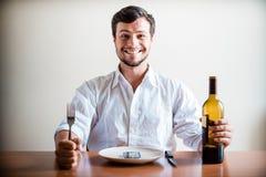 Ung stilfull man med den vita skjortan och telefonen på maträtten Arkivfoton