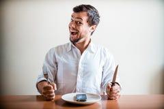 Ung stilfull man med den vita skjortan och telefonen på maträtten Royaltyfri Bild