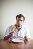 Ung stilfull man med den vita skjortan som äter moroten fotografering för bildbyråer