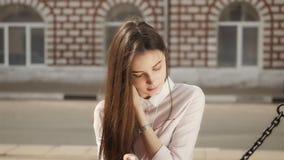 Ung stilfull nätt flicka med telefonen som poserar i stadsgatorna Tonårig modell med hörlurar arkivfilmer