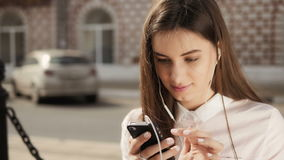 Ung stilfull nätt flicka med telefonen som poserar i stadsgatorna Tonårig modell med hörlurar stock video