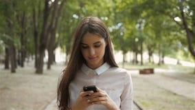 Ung stilfull nätt flicka med telefonen som poserar i stadsgatorna Tonårig modell med hörlurar lager videofilmer