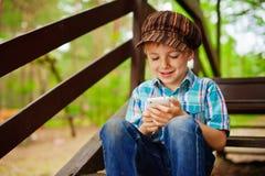 Ung stilfull pojke som bläddrar internet på mobil phon Arkivbilder