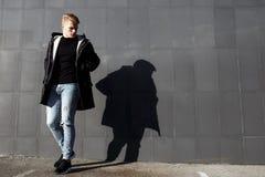 Ung stilfull rödhårig manman i den moderiktiga dräkten som poserar mot stads- bakgrund Arkivbild