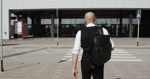Ung stilfull skallig affärsman som går till affärsmitten, flygplats, kontor Begrepp: en ny affär som reser världen lager videofilmer