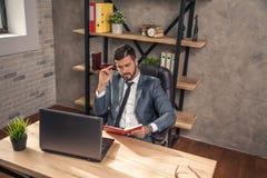 Ung stilfull stilig affärsman som arbetar i kontoret på hans skrivbord som gör att tänka för några anmärkningar fotografering för bildbyråer