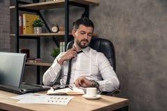 Ung stilfull stilig affärsman som arbetar på hans skrivbord i kontoret som fixar hans band och ser klockan royaltyfria foton