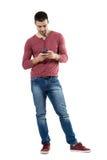 Ung stilfull tillfällig man som använder mobiltelefonen som ner ser på telefonen Arkivfoton