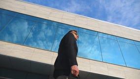Ung stilig affärsman med gå för portfölj som är utomhus- längs modern kontorsbyggnad Affärsman i sunglass Royaltyfri Bild