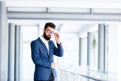 Ung stilig affärsman Posing At Workplace Arkivfoton