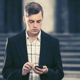 Ung stilig affärsman som använder den smarta telefonen i stadsgata Royaltyfri Fotografi