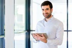 Ung stilig affärsman som använder hans touchpad som i regeringsställning står Royaltyfri Bild