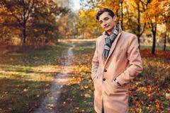 Ung stilig affärsman som går i höstskog på solnedgången Bärande klassikerkläder och tillbehör för stilfull grabb royaltyfria bilder