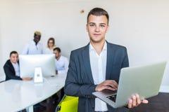 Ung stilig affärsman som ler och använder bärbara datorn, medan stå i regeringsställning, i bakgrunden annat arbeta för affärsmän royaltyfri fotografi