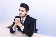 Ung stilig affärsman som ler och tänker på kontoret royaltyfria bilder