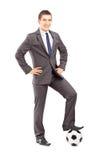 Ung stilig affärsman som poserar med en fotboll royaltyfri bild