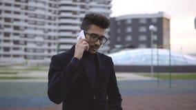 Ung stilig affärsman som talar på mobiltelefonen arkivfilmer