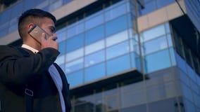 Ung stilig affärsman som talar på mobiltelefonen i staden lager videofilmer