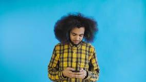 Ung stilig afrikansk amerikanman som använder telefonen på blå bakgrund Begrepp av sinnesr?relser arkivfilmer
