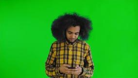 Ung stilig afrikansk amerikanman som använder telefonen på den gröna skärmen eller nyckel- bakgrund för chroma Begrepp av sinnesr stock video