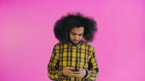 Ung stilig afrikansk amerikanman som använder telefonen på purpurfärgad bakgrund Begrepp av sinnesr?relser lager videofilmer