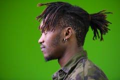 Ung stilig afrikansk man med dreadlocks som bär kamouflageskjortan fotografering för bildbyråer
