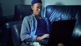 Ung stilig asiatisk man i exponeringsglas med reflexioner genom att använda hans bärbar dator som sitter i aftonen i rummet I dar lager videofilmer