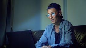 Ung stilig asiatisk man i exponeringsglas med reflexioner genom att använda hans bärbar dator som sitter i aftonen i rummet I dar arkivfilmer