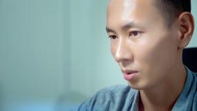 Ung stilig asiatisk man som använder hans bärbar dator som i regeringsställning sitter på skrivbordet arkivfilmer