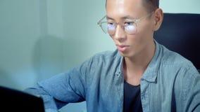 Ung stilig asiatisk man som använder hans bärbar dator som i regeringsställning sitter på skrivbordet stock video
