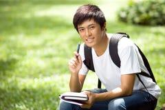 Ung stilig asiatisk student med bärbara datorn Arkivbild