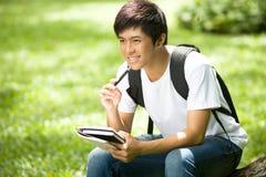 Ung stilig asiatisk student med böcker och leende i utomhus- Royaltyfri Fotografi