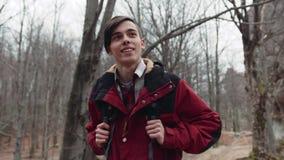 Ung stilig europeisk pojke med en stilfull frisyr i en sportdräkt med en turist- ryggsäck som carelessly igenom går lager videofilmer