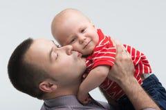 Ung stilig fader som kysser hans litet barnson arkivbild
