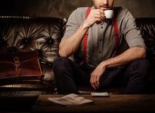 Ung stilig gammalmodig skäggig man med kopp kaffesammanträde på den bekväma lädersoffan på mörk bakgrund arkivbild