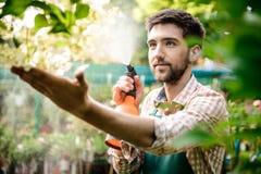 Ung stilig gladlynt trädgårdsmästare som ler, bevattna som tar omsorg av blommor Fotografering för Bildbyråer