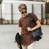 Ung stilig grabb i stilfulla kläder som går med en skateboard fotografering för bildbyråer