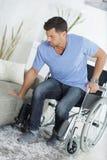 Ung stilig handikappad man som går från rullstolen till soffan fotografering för bildbyråer