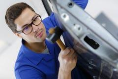 Ung stilig karosseritillverkare som reparerar den brutna bildörren arkivfoto