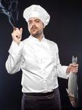 Ung stilig kock med den rökte bas- fisken för hav royaltyfri bild
