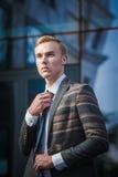 Ung stilig lyckad stilfull affärsman som står nära modernt kontor Royaltyfri Foto