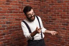 Ung stilig man i exponeringsglas som skrattar över tegelstenbakgrund Arkivfoton