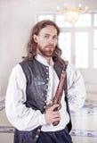 Ung stilig man i medeltida kläder med pistolen Royaltyfri Foto