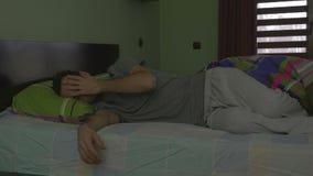Ung stilig man i säng som försöker att sova stock video