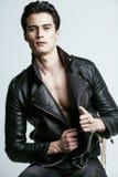 Ung stilig man, läder som silas på den nakna torson, emotionellt posera, vit bakgrund, modern grabb, livsstilfolk Royaltyfri Foto